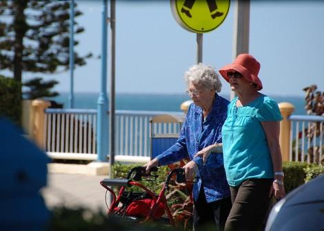 two women crossing beachside road, one using a walker