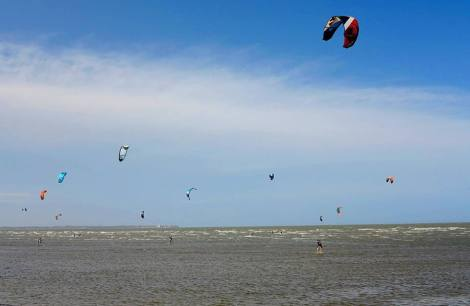The busy Sandgate foreshore was dotted with kitesurfers. Picture: Peter Bull (Canon G1X)