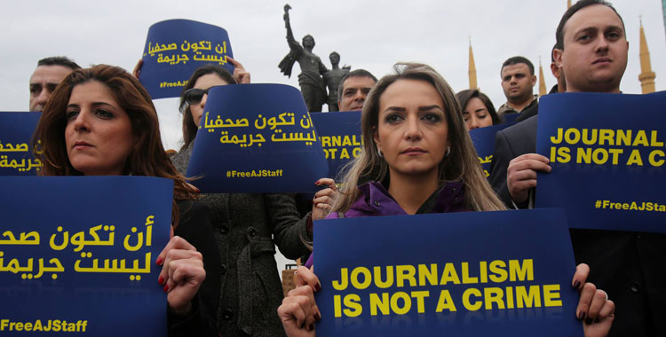 Protestors hold up signs saying 'Journalism is not a crime: Free AJ staff'